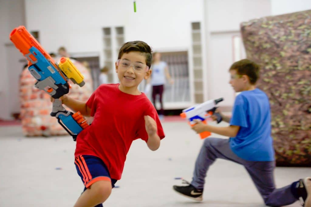young boy running with toy gun playing NERF hero