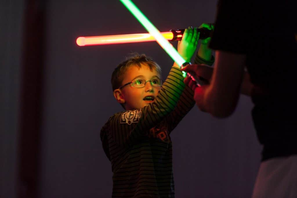 young boy fighting with light saber at force academy