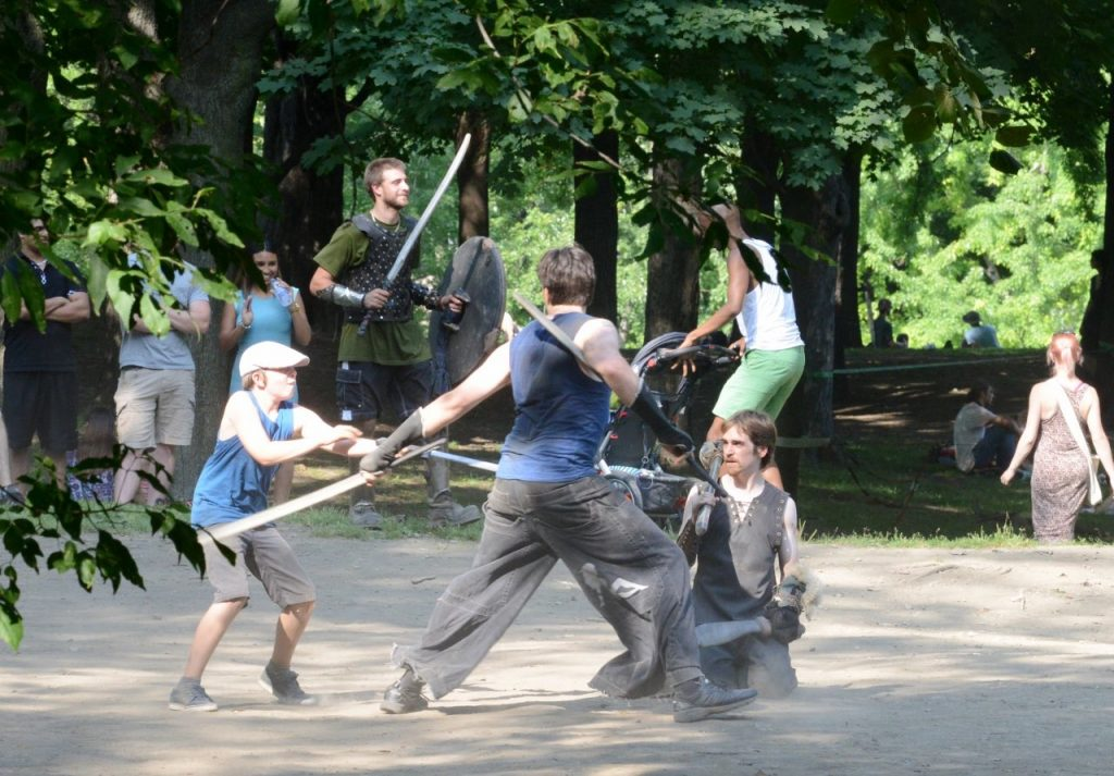 people fighting with foam swords in forest