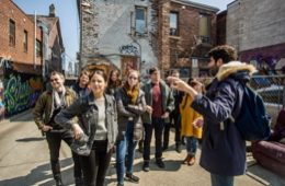 People discovering a back alley in the kensington market on a toronto food tour