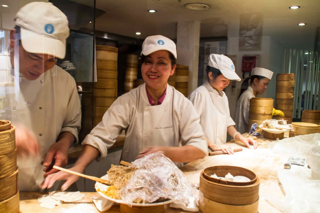 Cooks folding dumplings in a restaurant kitchen