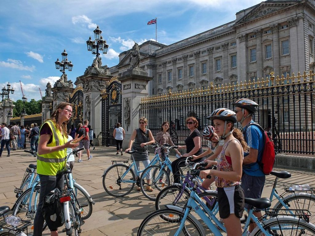 A London bike tours guide and tour group in front of Buckingham Palace