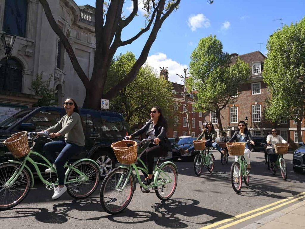 A London bike tours group cycle along a street