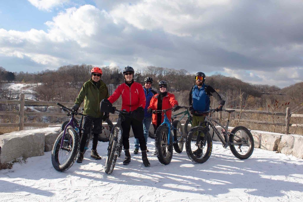group of cyclists at sweet pete's in toronto posing in front of evergreen brickworks winter scenery