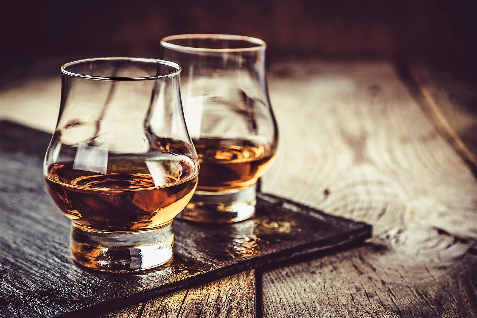 Close up shot of two glasses of whiskey set on a wooden table