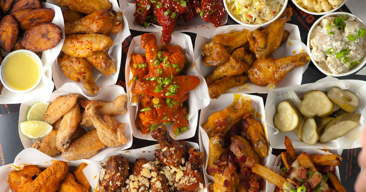 Overhead shot of various fried street foods. Chicken wings, potatoes, potato salad