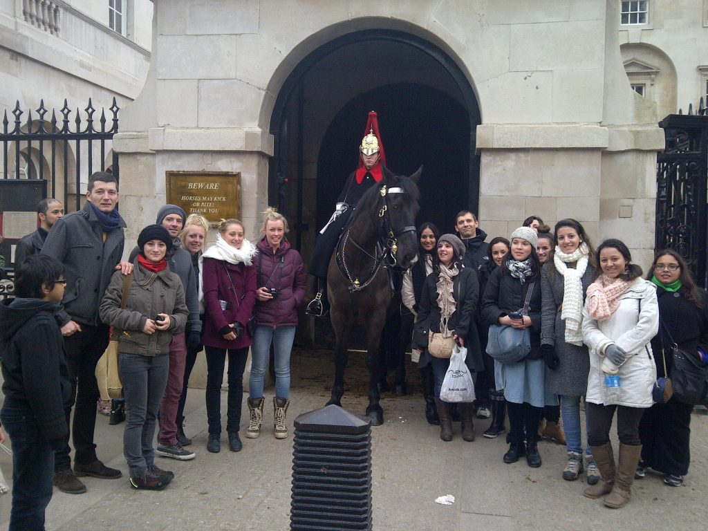 A London food tours group poses in front of Buckingham Palace guard
