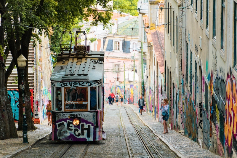 Yellow and white tram climbs steep Lisbon street
