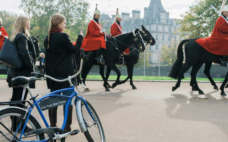 Two bicyclists taking a picture of royal guards on horses