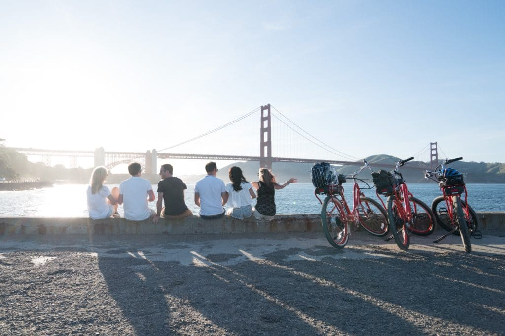 6 friends sitting on a pier in view of the Golden Gate Bridge, beside three bikes.