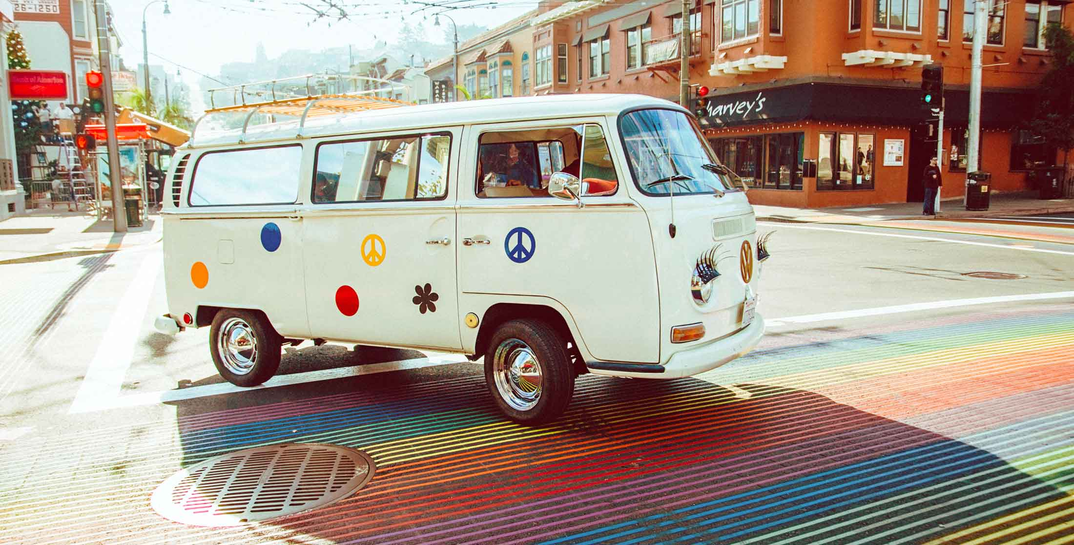 White classic Volkswagen camper bus adorned with hippie decals on a colorful street in San Fransisco