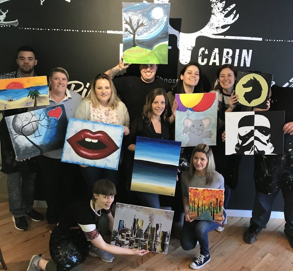 group posing with their canvases at paint cabin toronto