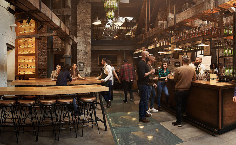 Group of people on a whiskey tour socializing with employees inside an expansive, modern pub.