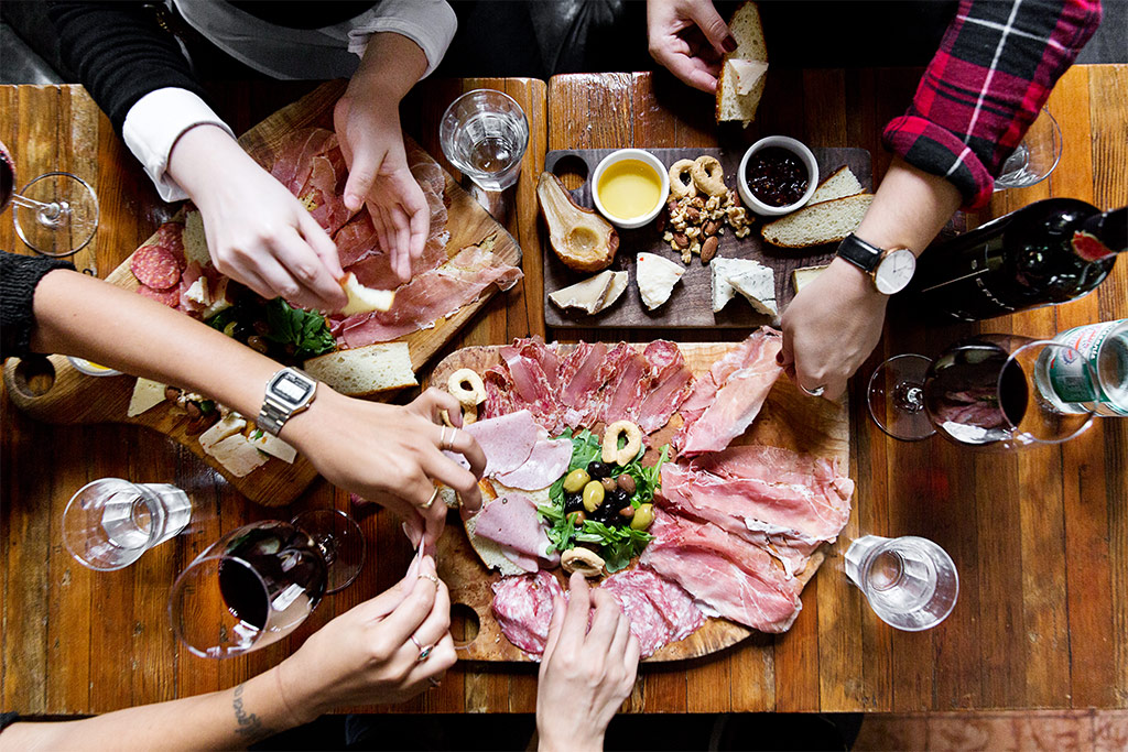 Group of people sharing charcuterie boards accompanied with wine on a wooden table