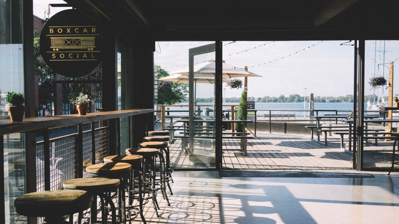 Open concept restaurant overlooking the water, featuring an expansive patio.