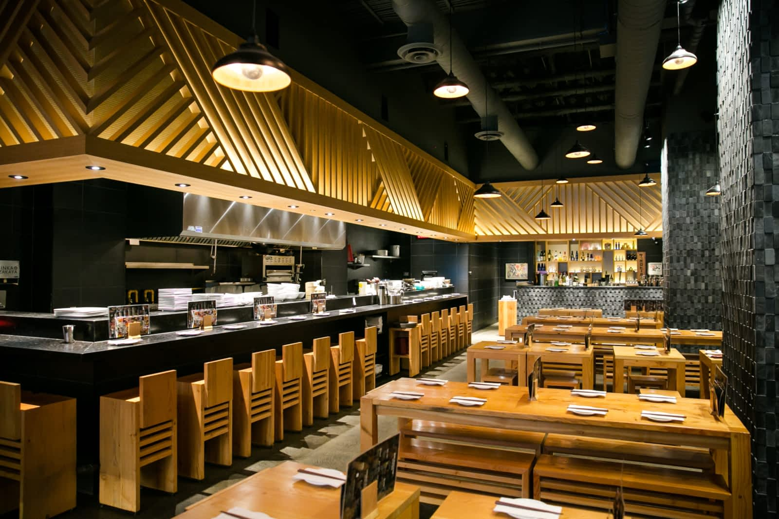 Modern Japanese restaurant featuring bar seating and an open kitchen as well as dining tables
